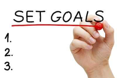 Hand underlining Set Goals with red marker isolated on white.